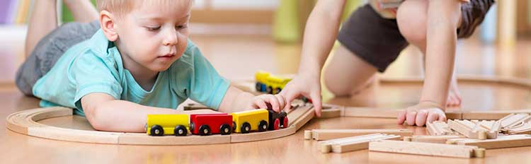 jungs-spielen-mit-holzeisenbahn